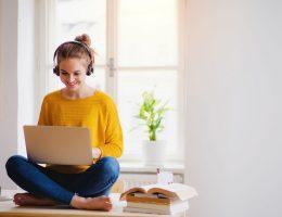 Uma estudante pós-graduanda sorridente estudando no seu notebook com fones de ouvido, sentada em uma mesa, de costas para a janela.